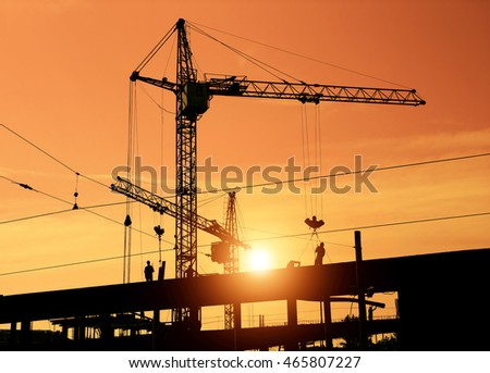 Construction cranes and construction workers on building site