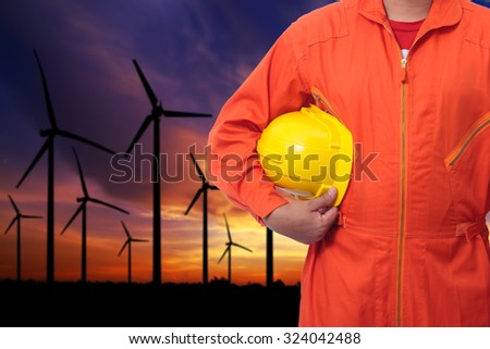 construction safety work concept of man worker holding hardhat  With wind turbine sunset background. - stock photo