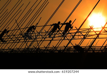 Construction workers working on scaffolding.The effect of backlight under the sunset silhouette.Yellow warm background photos.