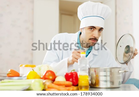 cook man  tasting soup with ladle from pan - stock photo