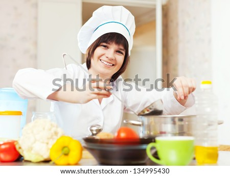 cook with ladle adds salt or spices into soup pan - stock photo