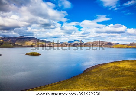 Cool blue water of the lake among the yellow tundra. The magic of summer in Iceland - stock photo