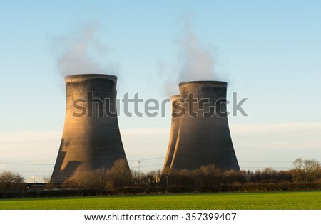 4 cooling towers at Fiddlers Ferry coal fired power station. Chimney stacks rise up above the greenery foreground.