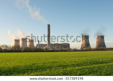 7 cooling towers at Fiddlers Ferry UK coal fired power station. Chimney stacks rise up above the greenery foreground.