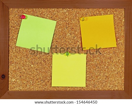 Cork bulletin board with blank sticky notes for text.                            - stock photo