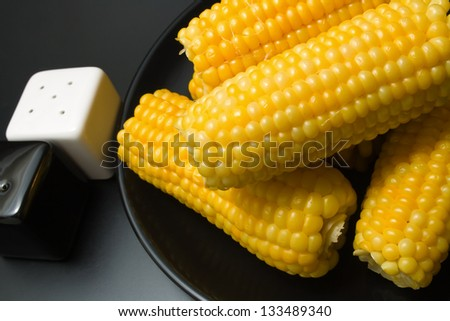 Corn cobs.  Freshly cooked corn cobs close-up arranged in a black ceramic plate with salt and pepper shakers on dark background - stock photo