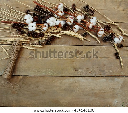 Cotton and wheat lying on a wooden background