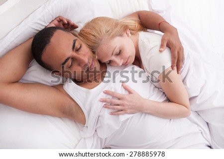 Couple asleep in a bed in an embrace