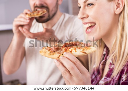 Couple having fun in the kitchen while eating pizza