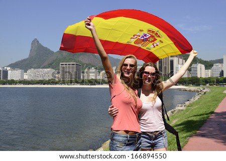 Couple of female sport fans holding a Spanish flag in Rio de Janeiro with Christ the Redeemer in the background. - stock photo