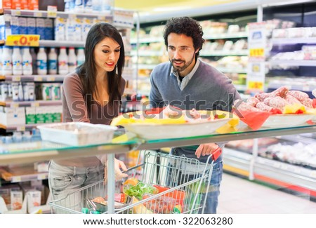 Couple shopping in a grocery store - stock photo