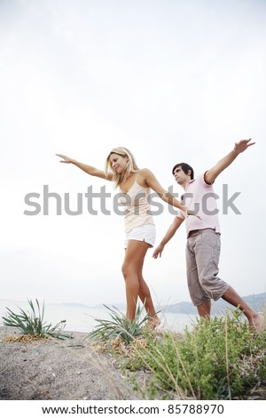 couple walking along the beach keeping balance with their hands - stock photo