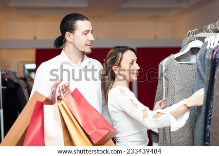 couple with shopping bags choosing sweater at  shop