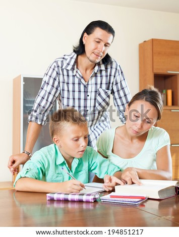 couple with teenager son doing homework in home interior