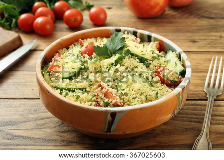 couscous salad in dish on rustic table  background