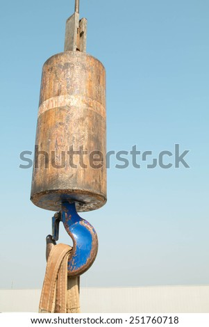 crane hook with some industrial buildings on the background  - stock photo