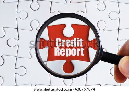 """Credit report"" text on red missing jigsaw puzzle with man right hand hold black magnifying glass searching for missing puzzle peace - business and finance concept - stock photo"