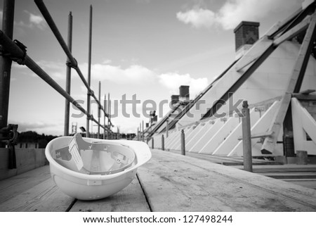 Crisis building industry. Conceptual image with empty building site and left helmet on scaffolding. - stock photo