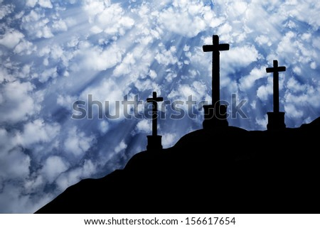 3 Crosses Silhouettes in a Cloudy Blue Sky - stock photo