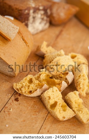 Crumbled bread on a wooden desk.Small pieces of white bread. Whole loafs on a background. Food, home-made bread, nobody, macro perspective - stock photo