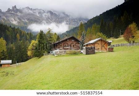18 0ctober 2016 , Dolomites Mountains ,Italy . Wooden house on a green meadow.