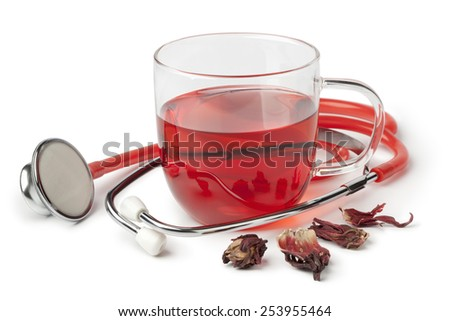 Cup of hibiscus tea and stethoscope on white background - stock photo