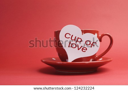 """Cup of love"" message on red polka dot cup and saucer against a red background for a bright and cheerful Valentines Day, Christmas, birthday or Mothers Day present with copy space for your text here. - stock photo"