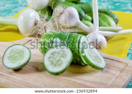 cut cucumbers an onions and garlic