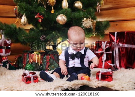 Cute baby boy with Christmas gifts - stock photo