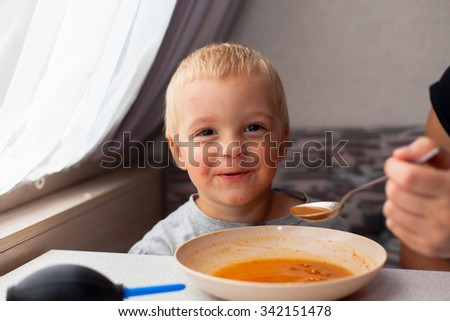 Cute blond boy eating lunch in a camper. (Shallow DOF) - stock photo