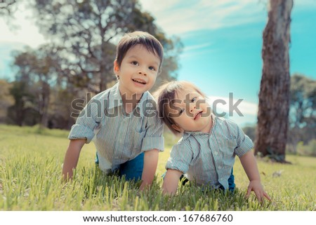 2 cute brothers playing outside in a grassy suburban park