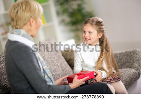 Cute girl giving her grandmother a gift, concept grandmother day - stock photo