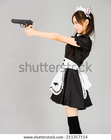 cute girl maid in gray background japanese style with gun - stock photo