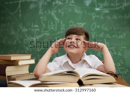 Cute little boy imagining during learning - stock photo