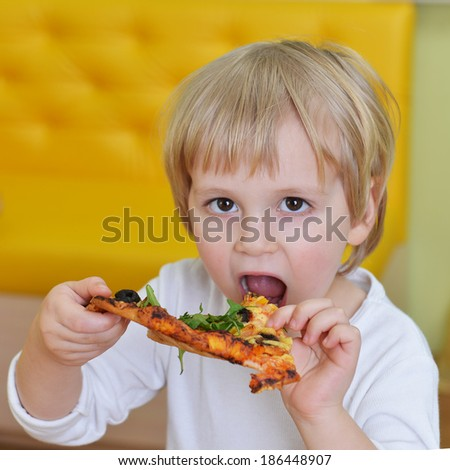cute little boy in white t shirt eats pizza