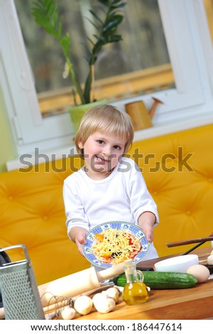 cute little boy in white t shirt shows cooked pizza