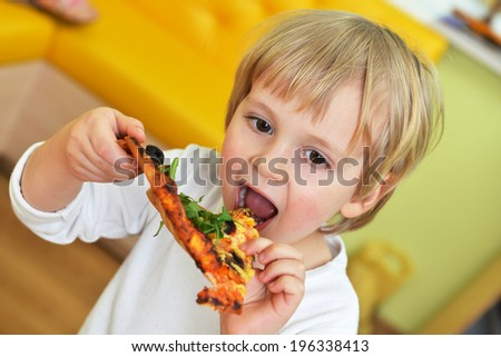 cute little boy in white tshirt eats pizza