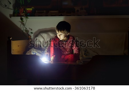 Cute little caucasian child, boy, reading book in bed under the covers at night. Children room, winter time - stock photo