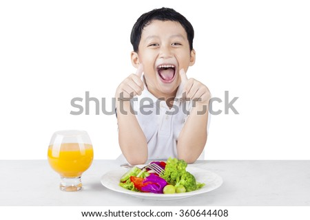 Cute little child making OK gesture while eating salad and juice, isolated on white background