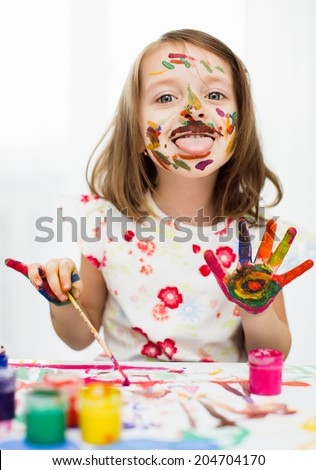 cute little girl is painting with gouache - stock photo