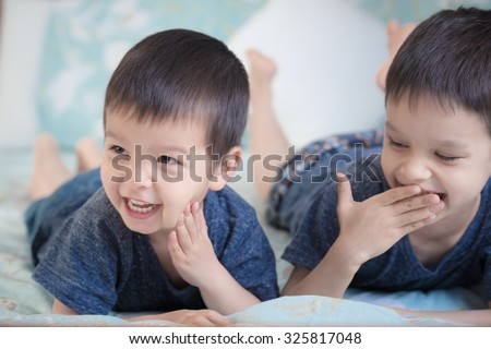 2 cute mixed race Asian Caucasian brothers laugh cheekily together inside on a bed - stock photo
