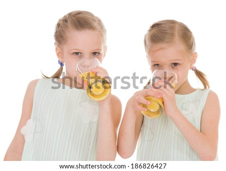 Cute sisters drink from a glass of fresh orange juice.Isolated on white background.