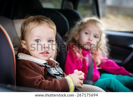 cute small children in car seats in the car - stock photo