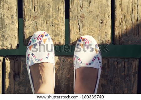 Cute white shoes from an aerial view on wooden background - stock photo