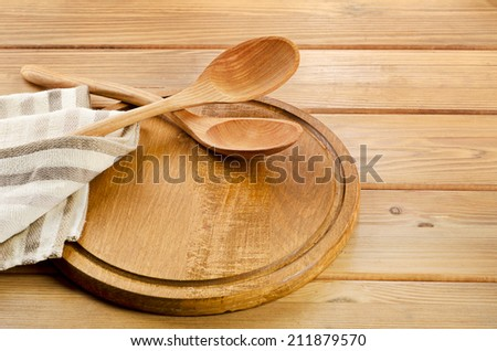 Cutting board and wooden spoons on planks  background