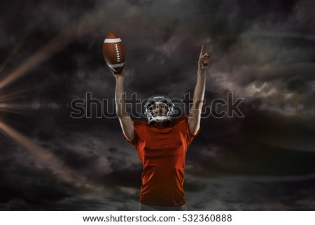 3D American football player with holding ball arms raised against gloomy sky