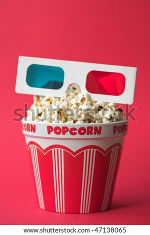 3D glasses on top of a bucket of popcorn - 3D cinema concept, shallow dof - stock photo