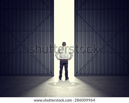 3d image of huge hangar doors and worker - stock photo
