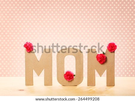 3D MOM Text with Fresh Carnation Flowers Standing on the Wooden Table with Pink Polka Dots Background - stock photo