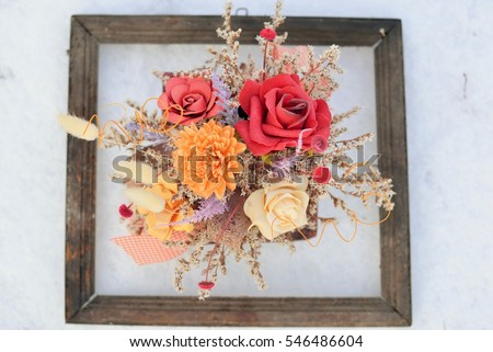 3d picture in nature. Dried flowers in a very old photo frame on snow